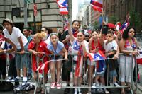 Onlookers wave Puerto Rican Flag and Cheer